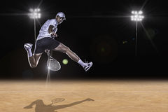 Tennis player reaching for the hard ball. Tennis player jumping for the ball from behind Royalty Free Stock Photo