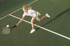 Tennis Player Reaching To Hit Ball. Female tennis player reaching to hit the tennis ball on court Royalty Free Stock Images