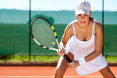 Tennis player ready for a serve. Portrait of a young tennis player standing ready for a serve Stock Photography