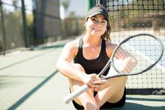 Tennis player resting from match. Portrait of young beautiful woman tennis player wearing cap having rest and sitting on tennis court  by the net after training Royalty Free Stock Photos