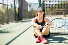 Tennis player resting after practice match. Beautiful hispanic female tennis player sitting relaxed on tennis court after practice match Royalty Free Stock Images