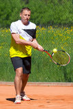 Tennis player on sand court. Tennis backhand with ball on racket on sand court Stock Photos
