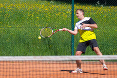 Tennis player on sand court. Ball leaves racket after forehand of tennis player Royalty Free Stock Image
