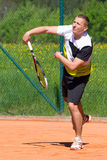 Tennis player on sand court. Tennis player after hitting service ball Stock Photography