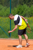 Tennis player on sand court. Tennis player prepares for service at court Royalty Free Stock Photo