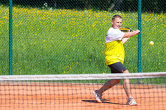 Tennis player on sand court. Slice backhand of tennis player behind net Royalty Free Stock Image