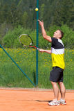 Tennis player on sand court. Tennis player throw up ball to make service Stock Photography
