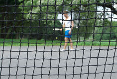 Tennis player seen through the net. Tennis player with racket and ball seen through the tennis net. Focus on the net royalty free stock image