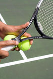 Tennis Player Serving Ball-Horizontal. A Tennis Player About to serve a ball. He is holding a racket and two balls in one hand. Horizontally framed shot Stock Photo