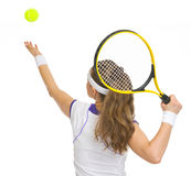 Tennis player serving ball. rear view Royalty Free Stock Photo
