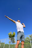 Tennis player serving playing outdoors - sport man. Tennis player serving playing outdoors sport. Man serve with throwing tennis ball up. Male athlete training Stock Images