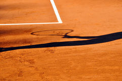 Tennis player shadow on a clay tennis court Stock Photography