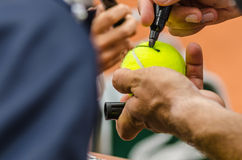 Tennis player signs autograph after win. Tennis player signs autograph on a tennis ball after win, closeup photo showing tennis ball and hands of a man making Royalty Free Stock Photos