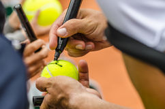 Tennis player signs autograph after win. Tennis player signs autograph on a tennis ball after win, closeup photo showing tennis ball and hands of a man making Royalty Free Stock Photo