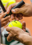 Tennis player signs autograph after win. Tennis player signs autograph on a tennis ball after win, closeup photo showing tennis ball and hands of a man making Stock Photo