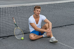 Tennis player sitting besides the net. On outdoor tennis court royalty free stock photography