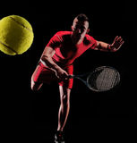 Tennis player. Sportive man playing tennis on black background Stock Photos