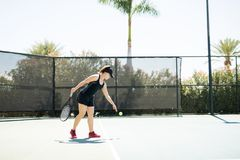 Female tennis player practising the serve. Tennis player standing on base line bouncing the ball, about to server during a tennis match Royalty Free Stock Photos