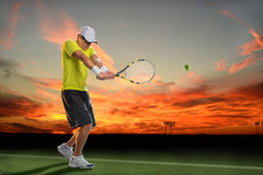 Tennis Player at Sunset. Hispanic tennis player hitting ball during sunset Royalty Free Stock Images