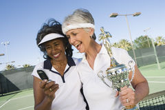 Tennis Player With Trophy Reading Text Message Royalty Free Stock Images