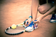 Tennis player tying shoelaces Stock Photo