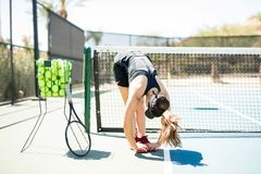 Tennis player warming up before practice. Female tennis player bending and touching her leg on tennis court before the training Royalty Free Stock Photo