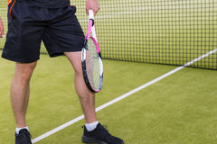 Tennis player warming up before tennis match. Tennis player wearing a sportswear warming up before tennis match on a court outdoor in summer or spring Royalty Free Stock Photography