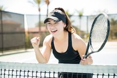 Tennis player winning a point. Cute young hispanic female tennis player in her 20s reacts after winning a point during match on court, player with clenched fist Stock Images