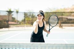 Tennis player winning a set. Pretty young female tennis player with clenched fist after winning a set on outdoor tennis court Stock Images