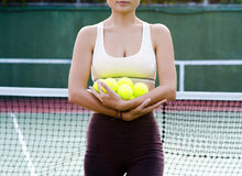 Tennis player. Woman with tennis balls on the court Stock Photography