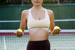 Tennis player. Woman with tennis balls on the court Stock Photo