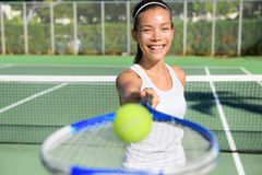 Tennis player - woman showing ball and racket. Tennis player portrait. Woman showing tennis ball and racket smiling happy. Female athlete inviting you to play Stock Photography