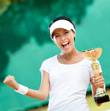 Tennis player won the cup. Female tennis player won the cup at the sport competition. Victory Royalty Free Stock Photos