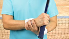 Tennis player with wrist pain. Shot of a tennis player with a carpal tunnel syndrome injury in the wrist on a clay court Royalty Free Stock Photography