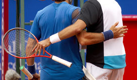 Tennis players embrace. Two tennis players embrace at the end of the match Stock Photos