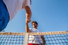 Tennis players holding hands. Two professional tennis players holding hands over tennis net before match Stock Photos