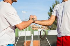 Tennis players holding hands. Two professional tennis players holding hands over tennis net before match Stock Photo