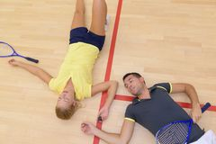 Tennis players laying down on court with racket. Tennis players laying down on the court with racket Royalty Free Stock Images