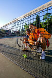 Tennis Players at the Net. Male and female tennis players crouching behind the net smiling.. They are holding rackets and two tennis balls are in front of them royalty free stock photography