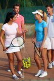 Tennis players prepared for mixed doubles. Smiling young tennis players prepared for mixed doubles Stock Photos