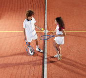 Tennis players with racket and ball standing in front of the net. Of court Stock Photography