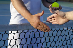 Tennis players shaking hands on the net Stock Photo