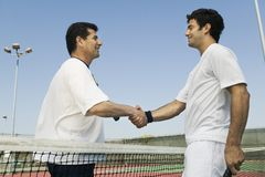 Tennis Players shaking hands over net on court side view Stock Image