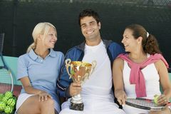 Tennis players sitting at tennis court man holding trophy front view portrait Stock Photo