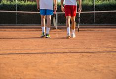 Tennis players walking towards net. Two professional tennis players with rackets walking towards tennis net Royalty Free Stock Photo