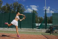 Advanced female player returns a ball during second set of International Cup. Tennis playing sportive woman hitting ball on red hard court. Caucasian athlete royalty free stock image