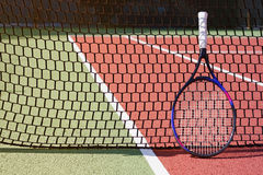 Tennis racket. Leaning against the net in a tennis court royalty free stock photo