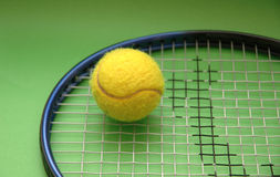 Tennis racket and ball. On green background stock photography
