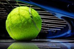 Tennis racket and ball. Tennis racquet resting on top of a tennis ball Royalty Free Stock Image
