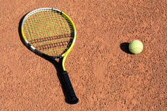 Tennis-racket and ball. Tennis-racket with one ball laying on the court Royalty Free Stock Photography
